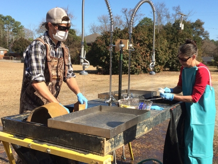 Figure 10. Large pieces of Alkaline Glazed Stoneware being washed outdoors using a table screen. Image Credit: Meg Gaillard/SCDNR.